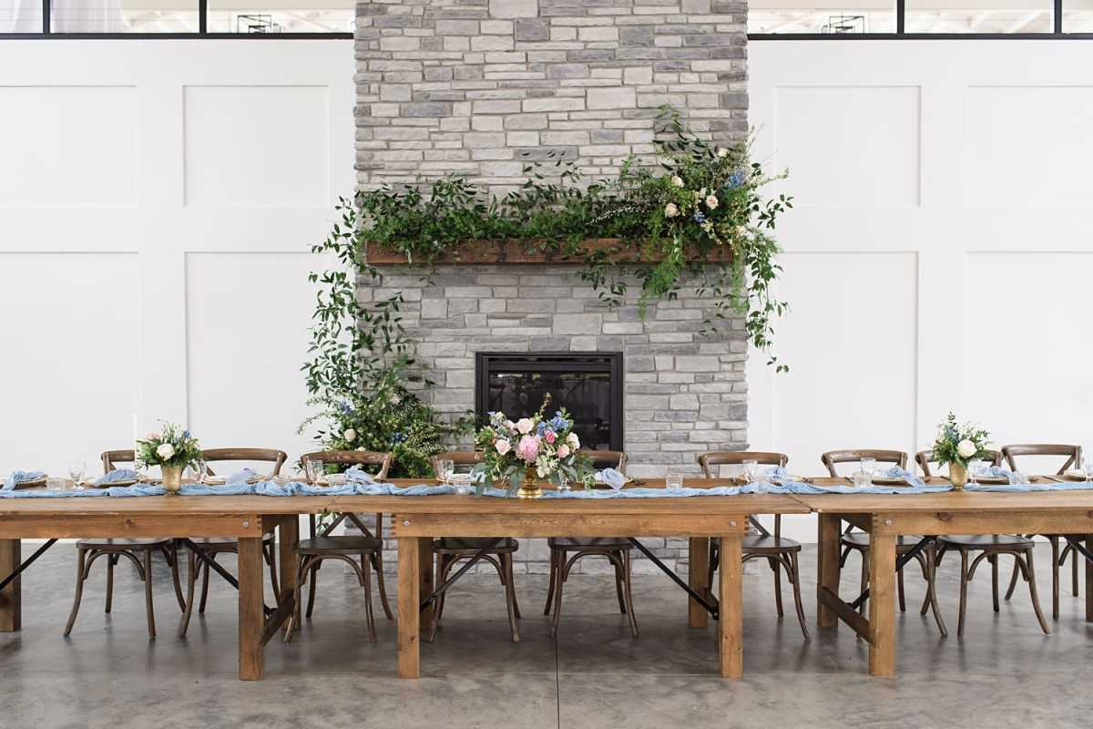 Farmhouse table with dusty blue runner and blush flowers at emerald hills event center in Promise City
