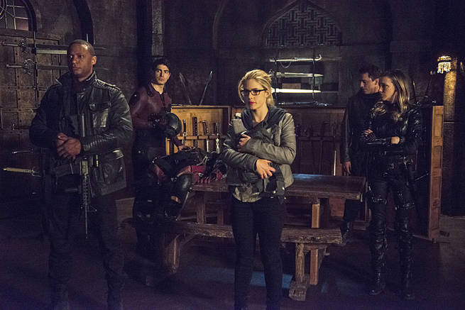 """Arrow -- """"My Name is Oliver Queen"""" -- Image AR323A_0307b -- Pictured (L-R): David Ramsey as John Diggle, Brandon Routh as Ray Palmer, Emily Bett Rickards as Felicity Smoak, John Barrowman as Malcolm Merlyn and Katie Cassidy as Laurel Lance -- Photo: Cate Cameron/The CW -- © 2015 The CW Network, LLC. All Rights Reserved."""