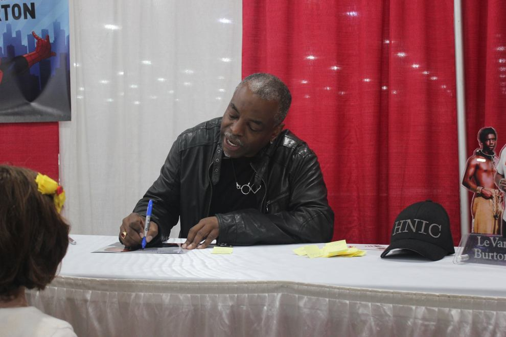 LeVar Buton signs an autograph for a young fan.