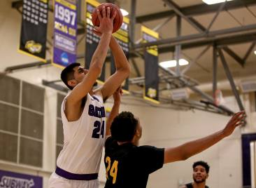 SF State Gators forward AJ Kahlon (24) scores over Cal State LA forward Brandon Hitchman (23) as the SF State Gators take on the Cal State LA Golden Eagles in a CCAA first round playoff game at SF State University in San Francisco, Calif., on Tuesday, February 28, 2017.