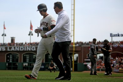 San Francisco Giants catcher Buster Posey (28) walks with trainer Dave Groeschner as he is taken out of the game after being hit by a pitch in the first inning as the Arizona Diamondbacks face the San Francisco Giants on opening day at AT&T Park in San Francisco, Calif., on Monday, April 10, 2017.