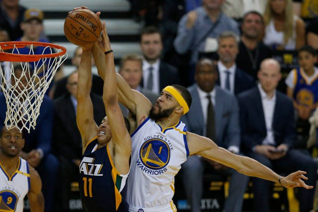 Golden State Warriors center Javale McGee (1) blocks the shot attempt by Utah Jazz guard Dante Exum (11) in the first half as the Utah Jazz face the Golden State Warriors at Oracle Arena in Oakland, Calif., on Monday, April 10, 2017.