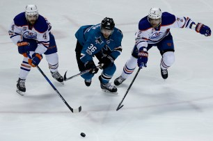 San Jose Sharks Jannik Hansen (36) races to the puck in front of Edmonton Oilers Kris Russell (4) and Andrej Sekera (2) as the Edmonton Oilers take on the San Jose Sharks at the SAP Center in San Jose, Calif., on Tuesday, April 18, 2017.