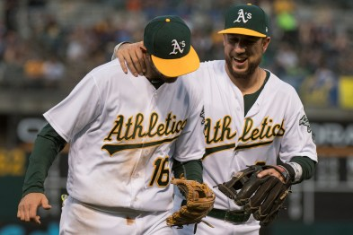 Oakland Athletics shortstop Adam Rosales (16) is congratulated by third baseman Trevor Plouffe (3) after making a diving play in the third inning of the game against the Boston Red Sox at the Oakland Coliseum in Oakland, Calif., on May 18, 2017.