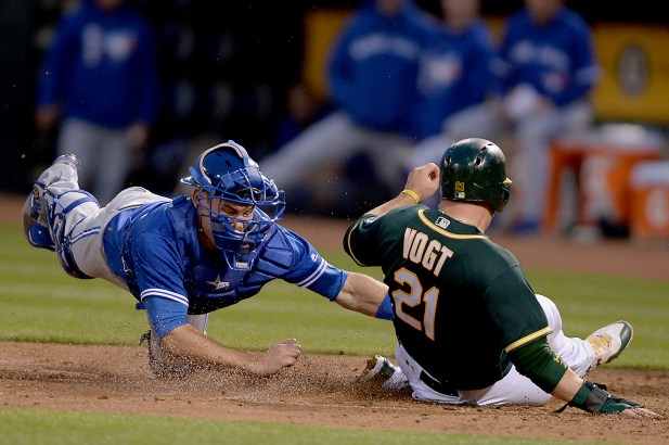 Toronto Blue Jays catcher Luke Maile (22) tags out Oakland Athletics catcher Stephen Vogt (21) in the fifth inning as the Toronto Blue Jays face the Oakland Athletics at Oakland Coliseum in Oakland, Calif., on Tuesday, June 6, 2017.