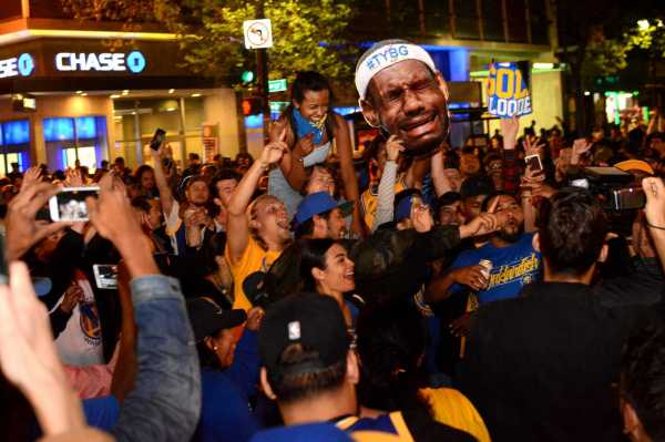 Golden State fans hold a cardboard cutout of Cleveland Cavaliers star LeBron James and shout into a television camera after the Warriors beat the Cavaliers to win the NBA Finals in Oakland, Calif. on Monday, Jun. 12, 2017.