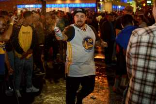 A Golden State Warriors fan sprays alcohol into a crowd after the Warriors beat the Cleveland Cavaliers to win the NBA Finals in Oakland, Calif. on Monday, Jun. 12, 2017.