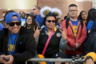 Jayne Laiprasert (middle), 36, a lawyer from Walnut Creek, Calif. wears homemade Warriors bunny ears and blue and gold earrings at the Golden State Warriors championship parade in Oakland, Calif. on Thursday, Jun. 15, 2017.