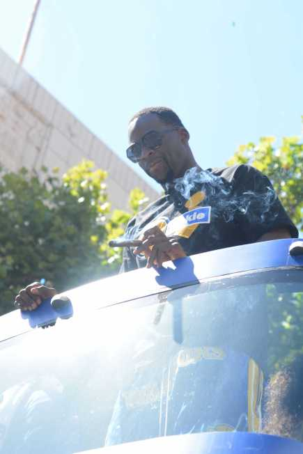 Warriors F Draymond Green smokes a cigar as he rides a double-decker bus at the Golden State Warriors championship parade in Oakland, Calif. on Thursday, Jun. 15, 2017.