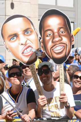 A fan holds caricatures of Warriors players at the Golden State Warriors championship parade in Oakland, Calif. on Thursday, Jun. 15, 2017.