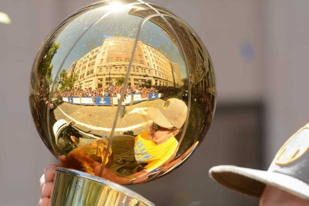 The crowd is reflected in the 2015 NBA Finals trophy at the Golden State Warriors championship parade in Oakland, Calif. on Thursday, Jun. 15, 2017.