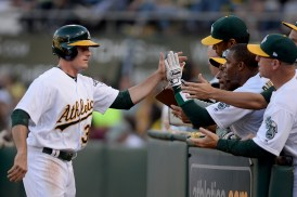 Athletics center fielder Jacob Brugman is congratulated after scoring in the second inning of Oakland's 7-6 win over the New York Yankees Friday night.