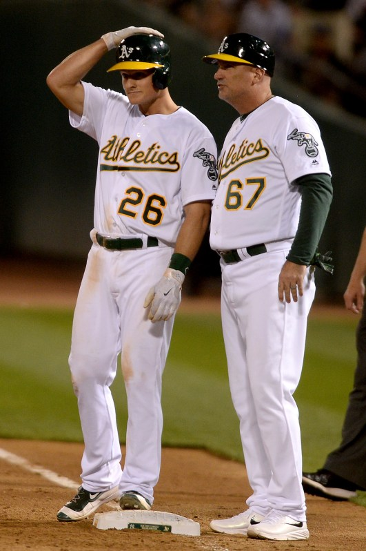 Oakland Athletics third baseman Matt Chapman (26) is congratulated by first base coach Steve Scarsone (67) after a hit in the eighth inning as the New York Yankees face the Oakland Athletics at Oakland Coliseum in Oakland, Calif., on Friday, June 16, 2017.
