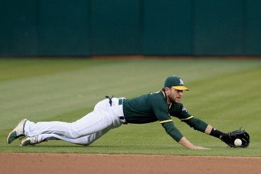 Oakland Athletics second baseman Jed Lowrie (8) dives to throw out Gattis in the fourth inning as the Houston Astros face the Oakland Athletics at Oakland Coliseum in Oakland, Calif., on Wednesday, June 21, 2017.