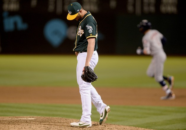 Oakland Athletics relief pitcher Josh Smith (57) looks down as Houston Astros shortstop Carlos Correa (1) rounds the bases after hitting a homer in the ninth inning as the Houston Astros face the Oakland Athletics at Oakland Coliseum in Oakland, Calif., on Wednesday, June 21, 2017.