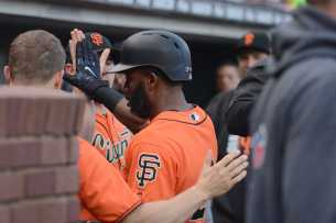 San Francisco Giants center fielder Denard Span (2) high fives his teammates as he scores a run in the first inning as the New York Mets face the San Francisco Giants at AT&T Park in San Francisco, Calif., on Friday, June 23, 2017.