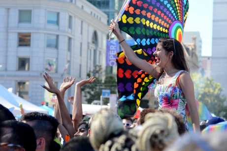 A Pride attendee waves a rainbow-and-black-colored heart flag while dancing to music at the Pride Celebration in San Francisco, Calif., on Sunday, June 25, 2017.