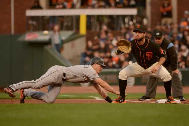Miami Marlins catcher J.T. Realmuto (11) slides safely back to first base during an attempted pickoff play in the fourth inning as the Miami Marlins face the San Francisco Giants at AT&T Park on Friday, July 8, 2017.