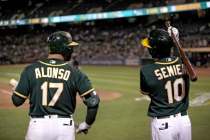 Oakland Athletics first baseman Yonder Alonso (17) and Oakland Athletics shortstop Marcus Semien (10) chat during a pitching change in the seventh inning as the Cleveland Indians face the Oakland Athletics at Oakland Coliseum in Oakland, Calif., on Friday, July 14, 2017.