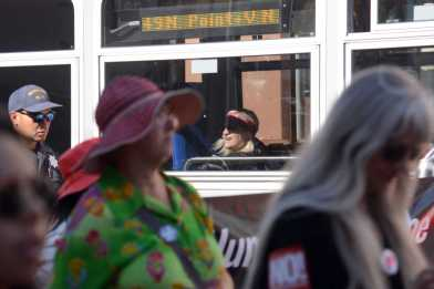 An onlooker watches an anti-Trump protest from a bus in San Francisco, Calif., on Saturday, July 15, 2017.