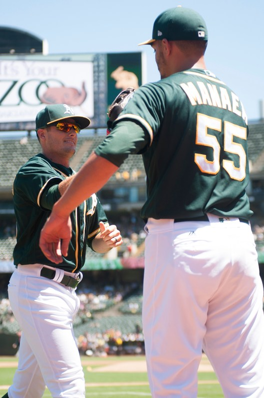 Oakland Athletics center fielder Jaycob Brugman (38) is congratulated by pitcher Sean Manaea (55) after making a leaping catch for the final out of the third inning of the game against the Cleveland Indians at the Oakland Coliseum in Oakland, Calif., on July 16, 2017.