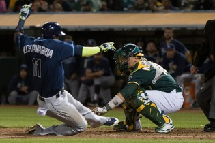 Oakland Athletics catcher Bruce Maxwell (13) tags Tampa Bay Rays shortstop Adeiny Hechavarria (11) out at home in the seventh inning of the game against the Tampa Bay Rays at the Oakland Coliseum in Oakland, Calif., on July 17, 2017.