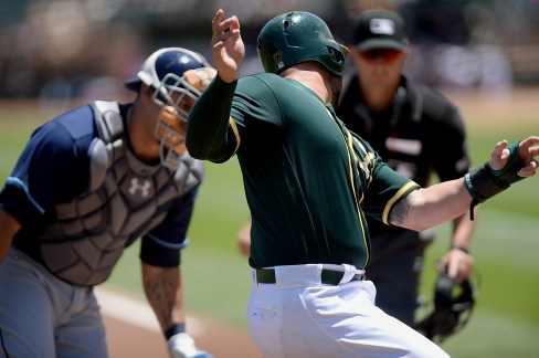 Oakland Athletics first baseman Yonder Alonso (17) is thrown out at home plate in the first inning as the Tampa Bay Rays face the Oakland Athletics at Oakland Coliseum in Oakland, Calif., on Wednesday, July 19, 2017.