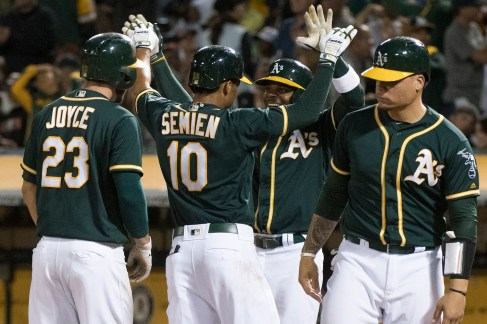 Oakland Athletics second baseman Marcus Semien (10) is congratulated at home after hitting a grand slam in the sixth inning of the game against the San Francisco Giants at the Oakland Coliseum in Oakland, Calif., on July 31, 2017.