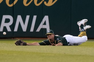 Oakland Athletics center fielder Jaycob Brugman (38) dives for the ball, but comes up short, in the fourth inning of the game against the San Francisco Giants at the Oakland Coliseum in Oakland, Calif., on July 31, 2017.