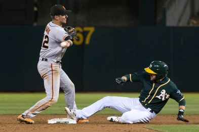 San Francisco Giants second baseman Joe Panik(12) forces Oakland Athletics second baseman Jed Lowrie (8) out at second as part of a double play in the sixth inning of the game against the Oakland Athletics at the Oakland Coliseum in Oakland, Calif., on July 31, 2017.