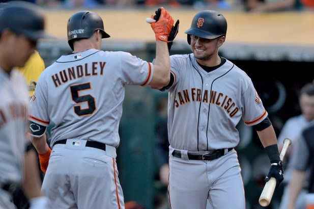 San Francisco Giants catcher Nick Hundley (5) is congratulated after a home run in the first inning as the San Francisco Giants face the Oakland Athletics at Oakland Coliseum in Oakland, Calif., on Tuesday, August 1, 2017.