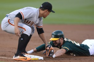 Oakland Athletics right fielder Matt Joyce (23) is tagged out by San Francisco Giants infielder Jae-Gyun Hwang (1) at third base attempting to steal as the San Francisco Giants face the Oakland Athletics at Oakland Coliseum in Oakland, Calif., on Tuesday, August 1, 2017.