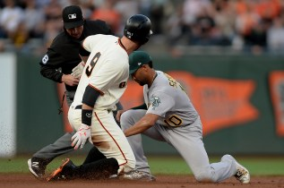 San Francisco Giants first baseman Brandon Belt (9) doubles under the tag of Semien in the first inning as the Oakland Athletics face the San Francisco Giants at AT&T Park in San Francisco, Calif., on Thursday, August 3, 2017.