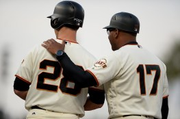 San Francisco Giants third base coach Jose Alguacil (17) talks with San Francisco Giants catcher Buster Posey (28) after a single as the Oakland Athletics face the San Francisco Giants at AT&T Park in San Francisco, Calif., on Thursday, August 3, 2017.