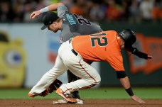 San Francisco Giants second baseman Joe Panik (12) is tagged by Arizona Diamondbacks second baseman Brandon Drury (27) attempting to advance on a fly ball in the sixth inning as the Arizona Diamondbacks face the San Francisco Giants at AT&T Park in San Francisco, Calif., on Friday, August 4, 2017.