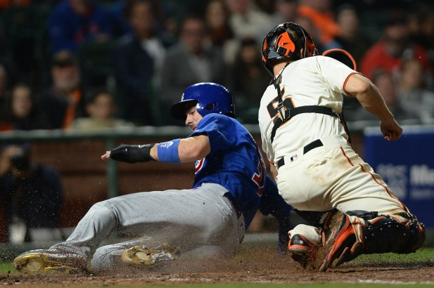 Chicago Cubs third baseman Kris Bryant (17) scores ahead of the throw to San Francisco Giants catcher Nick Hundley (5) as the Chicago Cubs face the San Francisco Giants at AT&T Park in San Francisco, Calif., on Tuesday, August 8, 2017.