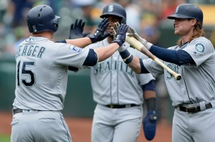 Seattle Mariners third baseman Kyle Seager (15) is congratulated after hitting a home run in the first inning as the Seattle Mariners face the Oakland Athletics at Oakland Coliseum in Oakland, Calif., on Wednesday, August 9, 2017.