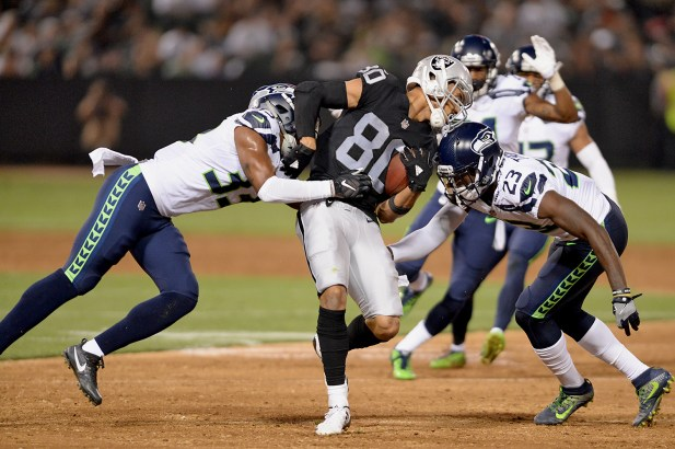 Oakland Raiders wide receiver K.J. Brent (80) fights for extra yardage in the first half as the Seattle Seahawks face the Oakland Raiders at Oakland Coliseum in Oakland, Calif., on Thursday, August 31, 2017.