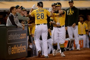 Oakland Athletics first baseman Matt Olson (28) is congratulated after a home run in the fifth inning as the Los Angeles Angels face the Oakland Athletics at Oakland Coliseum in Oakland, Calif., on Saturday, April 1, 2017.