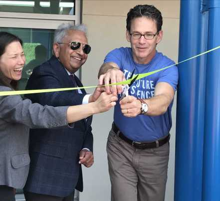 Genentech CEO Bill Anderson,South San Francisco Mayor Pradeep Gupta, and South San Francisco School Board Vice President Daina Lujan prepare to cut the ribbon Tuesday during the ceremony fro the Science Garage building at South San Francisco High on Tuesday, Sept. 5, 2017.