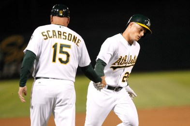 Oakland Athletics third baseman Matt Chapman (26) low fives Oakland Athletics third base coach Steve Scarsone (15) as he makes his way to home plate after hitting a home run during the second inning as the Houston Astros face the Oakland Athletics at the Oakland Coliseum on Friday September 08, 2017.