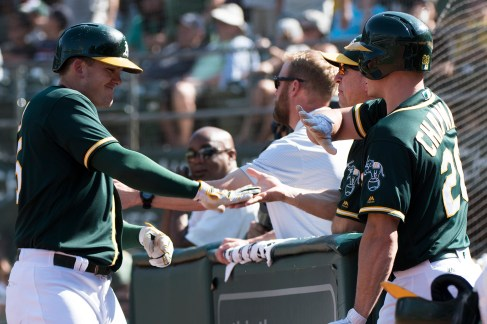 Oakland Athletics designated hitter Ryon Healy (25) is congratulated at the dugout after hitting a home run in the seventh inning of the game against the Houston Astros at the Oakland Coliseum in Oakland, Calif., on September 10, 2017.
