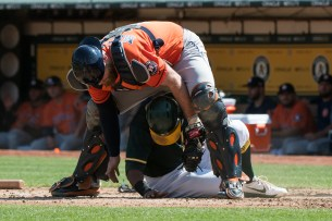 Oakland Athletics left fielder Khris Davis (2) is tagged out while sliding into home by Houston Astros catcher Brian McCann (16) in the fourth inning of the game at the Oakland Coliseum in Oakland, Calif., on September 10, 2017.