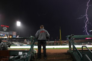 San Francisco Giants field security supervisor Carlos Carrillo looks on during a lightning storm as the Los Angeles Dodgers face the San Francisco Giants at AT&T Park in San Francisco, Calif., on Monday, September 11, 2017.