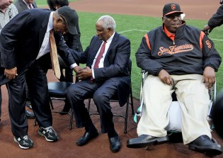 Hall of Famers Frank Robinson,center, helps Willie Mays to his seat along with Willie McCovey as the Giants celebrate African American Heritage Night before the Los Angeles Dodgers face the San Francisco Giants at AT&T Park in San Francisco, Calif., on Wednesday, September 13, 2017.