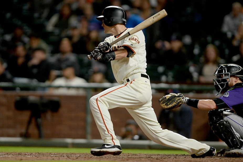 San Francisco Giants second baseman Kelby Tomlinson (37) singles in the ninth inning as the Colorado Rockies face the San Francisco Giants at AT&T Park in San Francisco, Calif., on Tuesday, September 19, 2017.