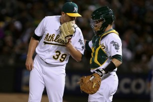 Oakland Athletics relief pitcher Blake Treinen (39) and Oakland Athletics catcher Dustin Garneau (12) communicate in the ninth inning as the Texas Rangers take on the Oakland Athletics at the Oakland Coliseum in Oakland, Calif. on Saturday, September 23, 2017.