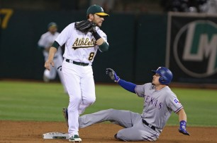 Oakland Athletics second baseman Jed Lowrie (8) gets an out at second in the ninth inning as the Texas Rangers take on the Oakland Athletics at the Oakland Coliseum in Oakland, Calif. on Saturday, September 23, 2017. Athletics won 1-0.