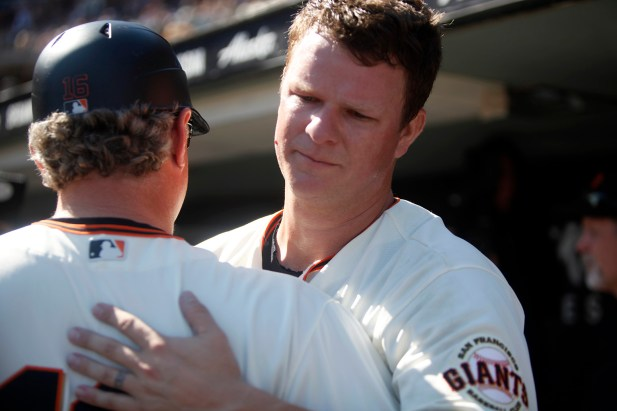 San Francisco Giants pitcher Matt Cain (18) hugs San Francisco Giants third base coach Phil Nevin (16) in the dugout after pitching his last inning as the San Diego Padres take on the San Francisco Giants at AT&T Park on Saturday, September 30, 2017.