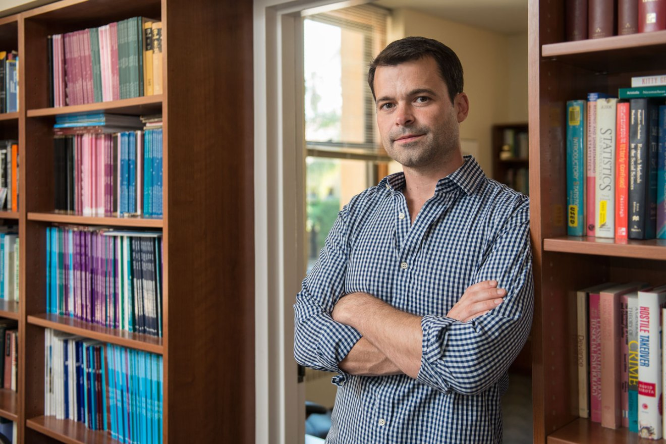 Robb Willer standing in front of a bookcase in his office